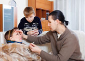 Man and son caring for sick woman — Stock Photo
