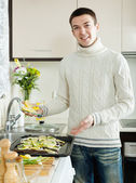 Man putting pieces of lemon in fish — Stock Photo