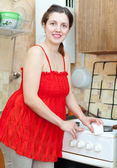 Happy woman in red cleans gas stove with sponge — Foto Stock
