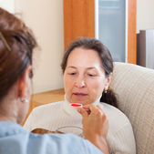 Girl giving the cough syrup to mature woman — Stock Photo