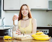 Woman making beverages with blender from bananas — Stock Photo