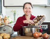 Woman cooking soup with mushrooms — Stock Photo