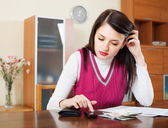 Serious housewife filling in utility payments bills — Stock Photo