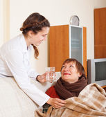 Smiling nurse in uniform caring for mature woma — Stock Photo