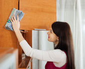 Brunette girl wiping dust from furniture — Stock Photo