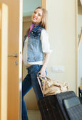 Positive woman with luggage leaving home — Stock Photo