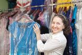 Mature woman chooses dress at shop — Stock Photo