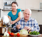 Ordinary senior couple cooking with vegetables — Stock Photo