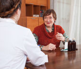 Woman speaking the doctor the symptoms of pain — Stockfoto