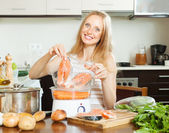 Woman cooking salmon fish and vegetables — Stock Photo
