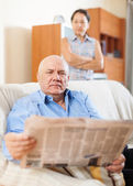 Mature man reading newspaper against sad woman — Photo
