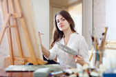 Long-haired young woman paints on canvas — Stock Photo