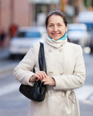 Mature woman at city street in autumn — Stock fotografie