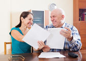 Happy senior couple holding documents at home — Stock Photo
