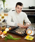 Man putting fish into sheet pan — Stock Photo