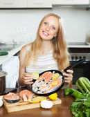 Smiling woman putting pieces lemon in fish — Stock Photo