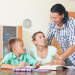 Couple with teenager schoolboy doing homework — Stock Photo #46908459