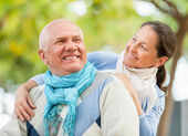 Happy mature couple together against blured trees — Stock Photo