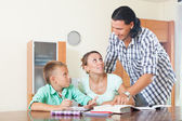 Couple with teenager schoolboy doing homework — Stock Photo