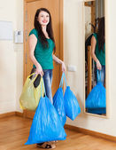 Happy  woman near door with garbage — Stock Photo