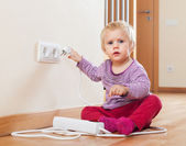 Baby playing with electrical extension — Stock Photo