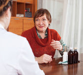 Woman complaining to  doctor about feels  — Stock Photo