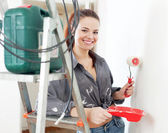 woman in grey shirt paints wall with roller — Stock Photo