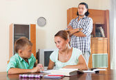 Couple with schoolboy doing homework — Stock Photo