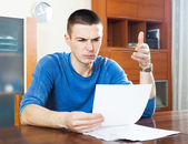 Sad frustrated man looking at piece of paper — Stockfoto