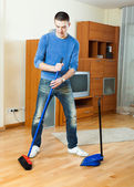man  sweeping the floor  at home — Stock Photo