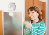 Smiling woman dusting glass — Stock Photo