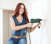 Happy woman in overalls with drill   — Stock Photo