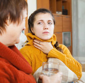 Woman giving glass of water to unwell friend   — Stock Photo