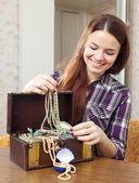 Happy girl chooses jewelry in treasure chest — Stock Photo