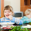 Emotional happy children eating at table — Stock Photo