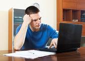 Sad confused man looking at laptop — Stockfoto