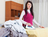 Young woman ironing with iron   — Photo
