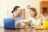 Couple looking e-mail in laptop during breakfast — Stock Photo