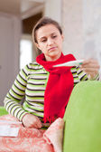 Sick woman looks by thermometer  — Stock Photo