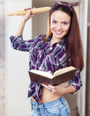 Woman reads book for recipe — Stock Photo