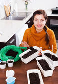 Girl sowing seeds in pots — Stock Photo