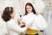 happy women chooses fur cape at wedding store  — Stock Photo