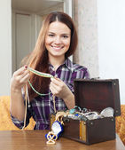 Woman chooses jewelry in treasure chest — 图库照片