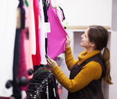 woman choosing shirt at clothing store — Stock Photo