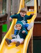 Happy children on slide at playground — Stockfoto