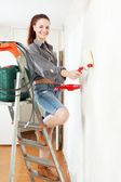 Happy girl makes repairs  at home — Stock Photo