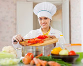 Happy  cook in toque works with vegetables — Stock Photo
