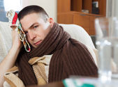Illness guy in plaid stuping  towel  — Stock Photo