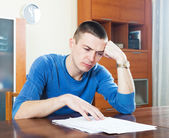Sad man looking at financial document in frustration — Stock Photo