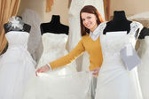 Bride chooses wedding gown at bridal boutique — Stock Photo